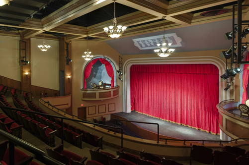 A photo of the interior of the Athens Theatre, which features rich red main drape and the detailed ceiling. Photo by Jeffrey Scott Zipay.